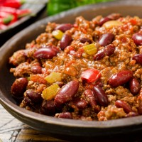 A hot spicy bowl of chili con carne with peppers.