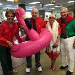 A group of residents take a picture with the flamingo float.