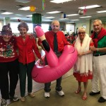 A group of residents wearing their red and green pose with the flamingo float