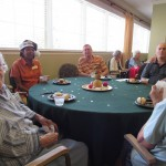 Our residents from The Gardens enjoying their snacks at the table.