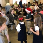 The kids passing out their gifts and receiving candy canes.