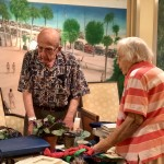 Veteran Ed Krys helping a fellow resident customer with her sale.