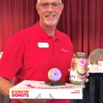 Larry Pinkerman of Bayada sporting his You Glazed It for Alzheimer's trophy, winner donuts and his fund jar.